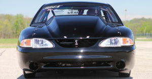 A close up of the front end of a black drag racing car